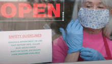 "A woman wearing a blue mask puts on blue latex gloves behind a window with an ""Open"" sign in it."